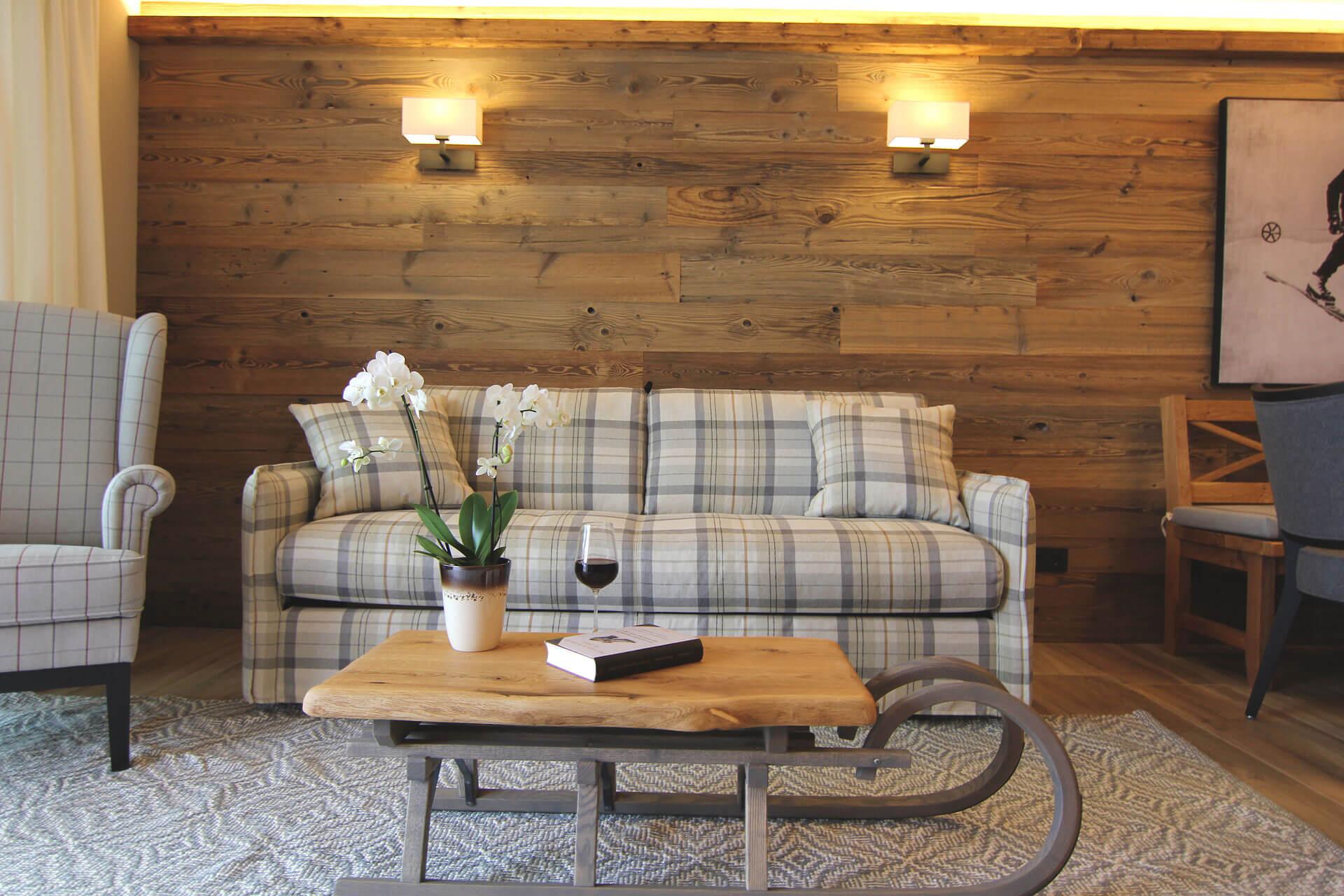 Wohnzimmertisch mit Glas Wein darauf in der Alpenrosen Lodge im Almlodge Westendorf