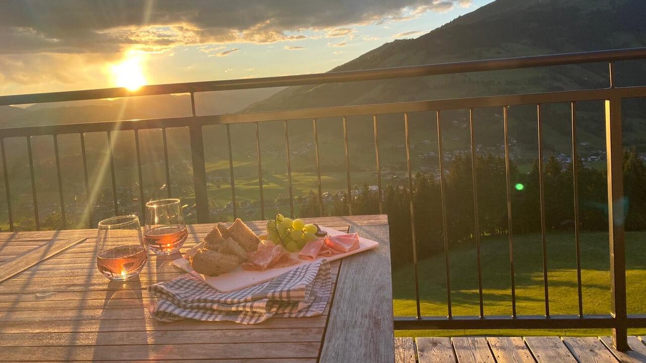 Sonnenuntergangsstimmung auf dem Balkon der Almlodge Westendorf